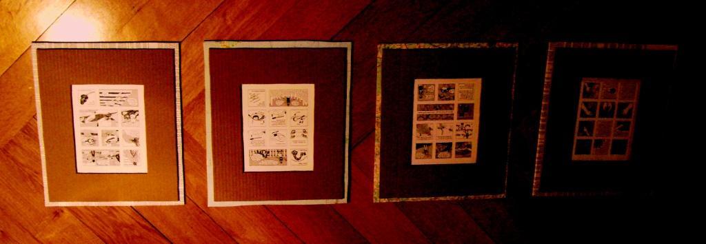 Foto von vier in Pappe gerahmtem Minicomic auf einem Parkettboden.