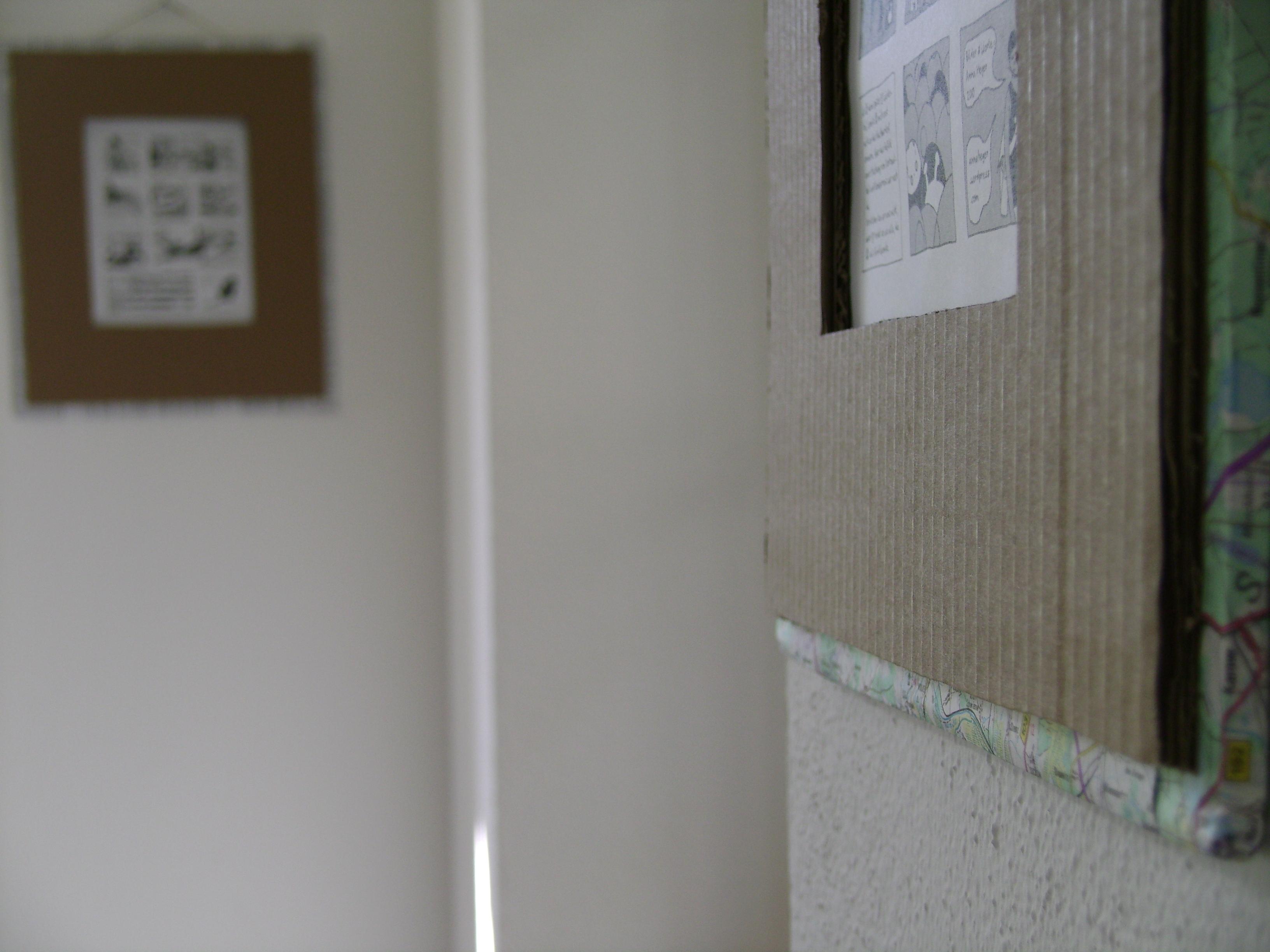 Foto von in Pappe gerahmten einseitigen Comics an einer weissen Raufasertapete.