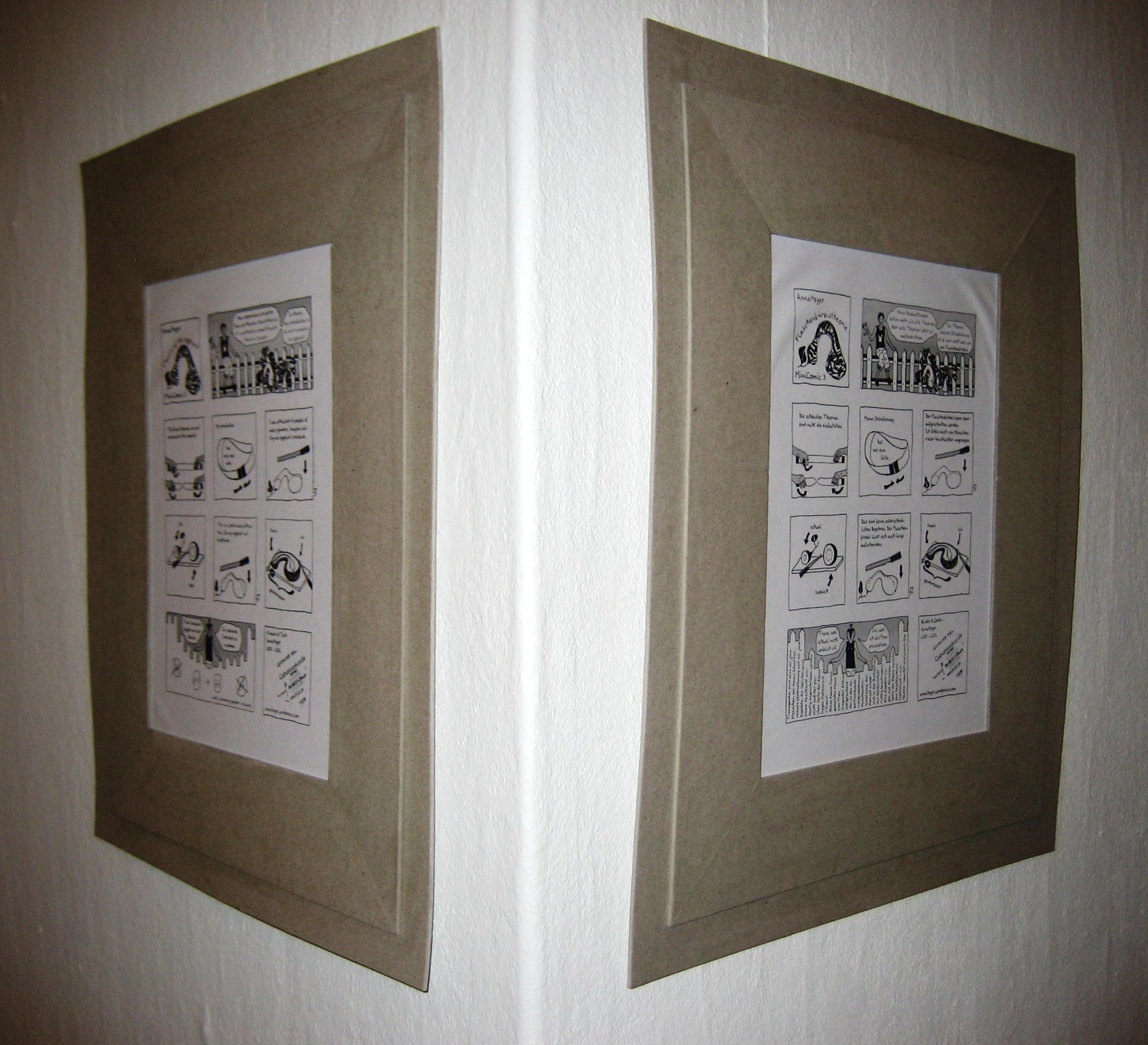 Foto der beiden Comics in grauer Pappe gerahmt an über Eck liegenden weißem Wänden