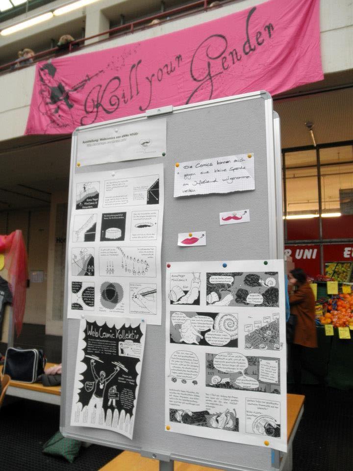 Foto. Auf einer Stellwand die beiden ausgedruckten Comics in einem Saal. Im Hintergrund ein Banner aus pinkem Stoff mit einer Disneyprinzessin und der Aufschrift: Kill your Gender
