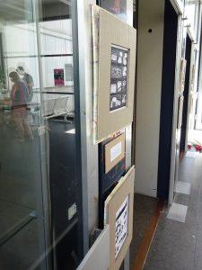 Foto der mit Rahmen aus Pappe gehängten, einseitigen Minicomics, daneben in der Glasscheibe spiegeln sich Besucher des Togetherfestes.