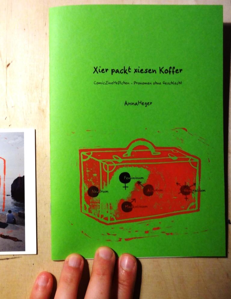 """Foto: DIN A5 Zine mit grünen Einband ist auf der Titelseite aufgeschlagen """"Xier packt xiesen Koffer"""
