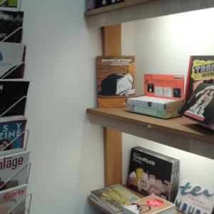 Kiste mit Minicomics in einem Regal im Buchladen