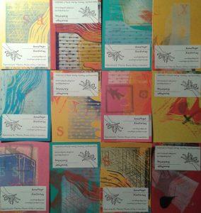 Visitenkarten von Anna Heger mit bunten Linoldruckmotiven auf gefärbtem Karton