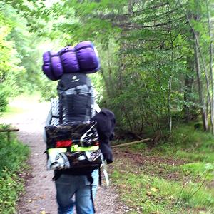 Foto einer Person mit vollbepackten Wanderrucksack, oben drauf eine Schlafsack und hinten dran etwas großes rechteckiges in einer Plastiktüte.