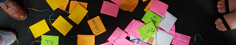 Foto von bunten Post-Its, die mit einer Schnur verbunden sind. Darauf stehen Label wie pan, lesbisch, hetero life und FTM.