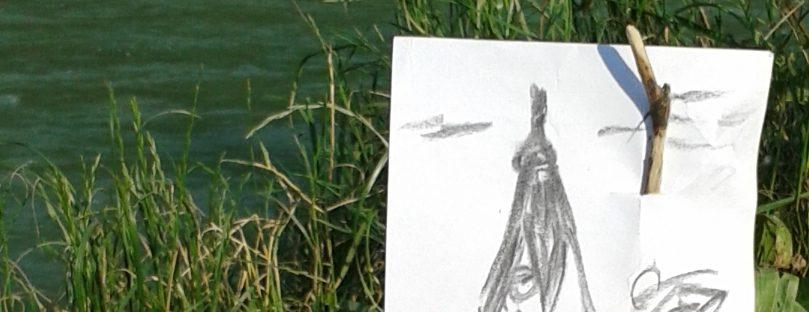 Foto, grobe Zeichnung wurde auf einen Ast gespießt, der am Fluss im Sand steckt