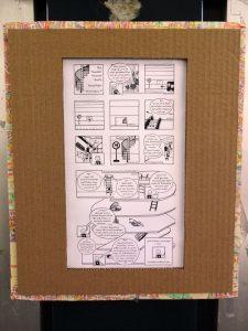 """Foto: Minicomic """"Die Hunderprozentquote"""" in Bilderrahmen aus brauner Pappe mit zwei Fäden an der Wand gehängt."""