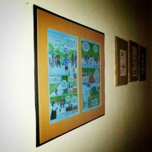 Foto: In brauner Papper gerahmte Comics hängen an einer weissen Wand.