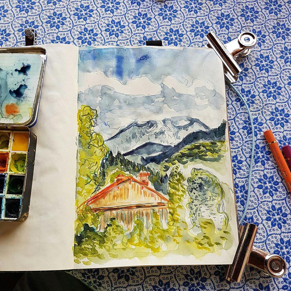 Foto: Skizzenbuch mit bunter alpiner Zeichnung. An den Ecken Metallklammern und links ein Miniaquarellkasten.