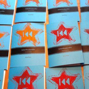 """Foto: viele blaue DINA5 Zines mit schwarzem Aufdruck """"Unterdruckarchiv"""" und linolgedruckten organenen Sternen."""