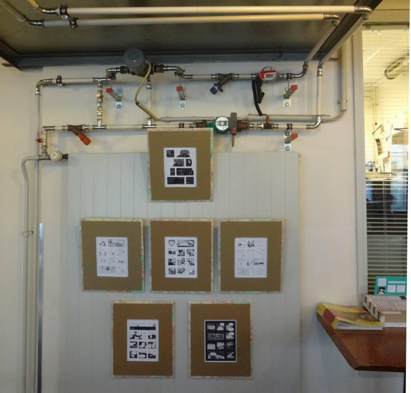 Foto: 6 Comics mit Rahmen aus brauner Pappe hängen vor weisser Heizung mit vielen Rohren darüber.