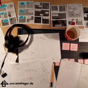 Foto: viele Blätter mit ausgedruckten Comicentwürfen und Korrekturen liegen auf einem Schreibtisch, ausserdem pinke Post-it Notzizettel, ein Notizbuch und eine Teetasse.