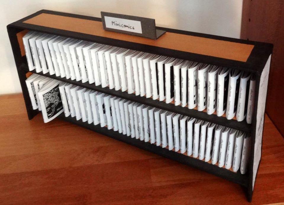 Foto: Aufsteller aus brauner Pappe und schwarzem Papier mit 25 Minicomics in 2 Etagen.