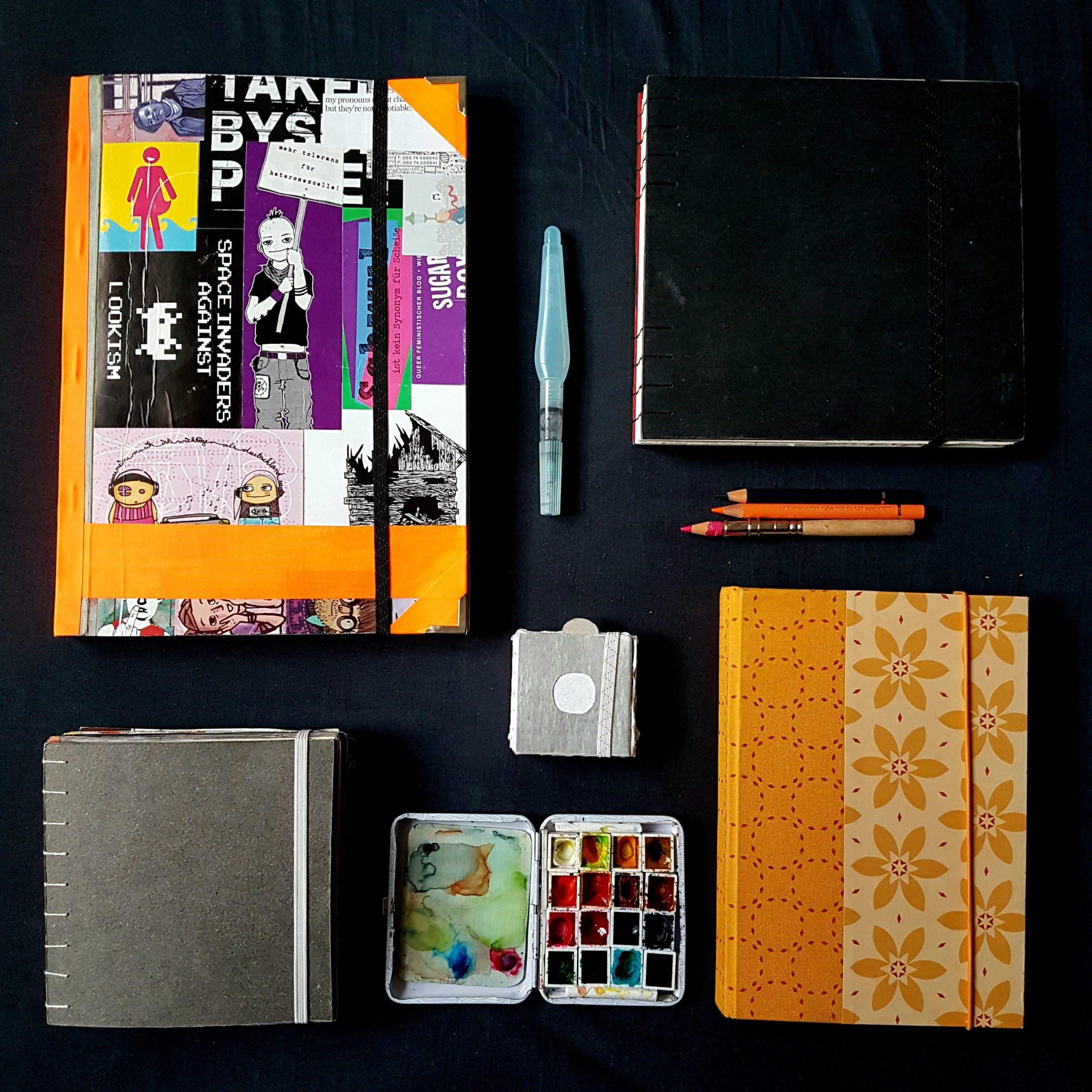 Foto: 5 unterschiedliche Skizzenbücher auf schwarze Tischdecke mit Miniaquarellkasten.