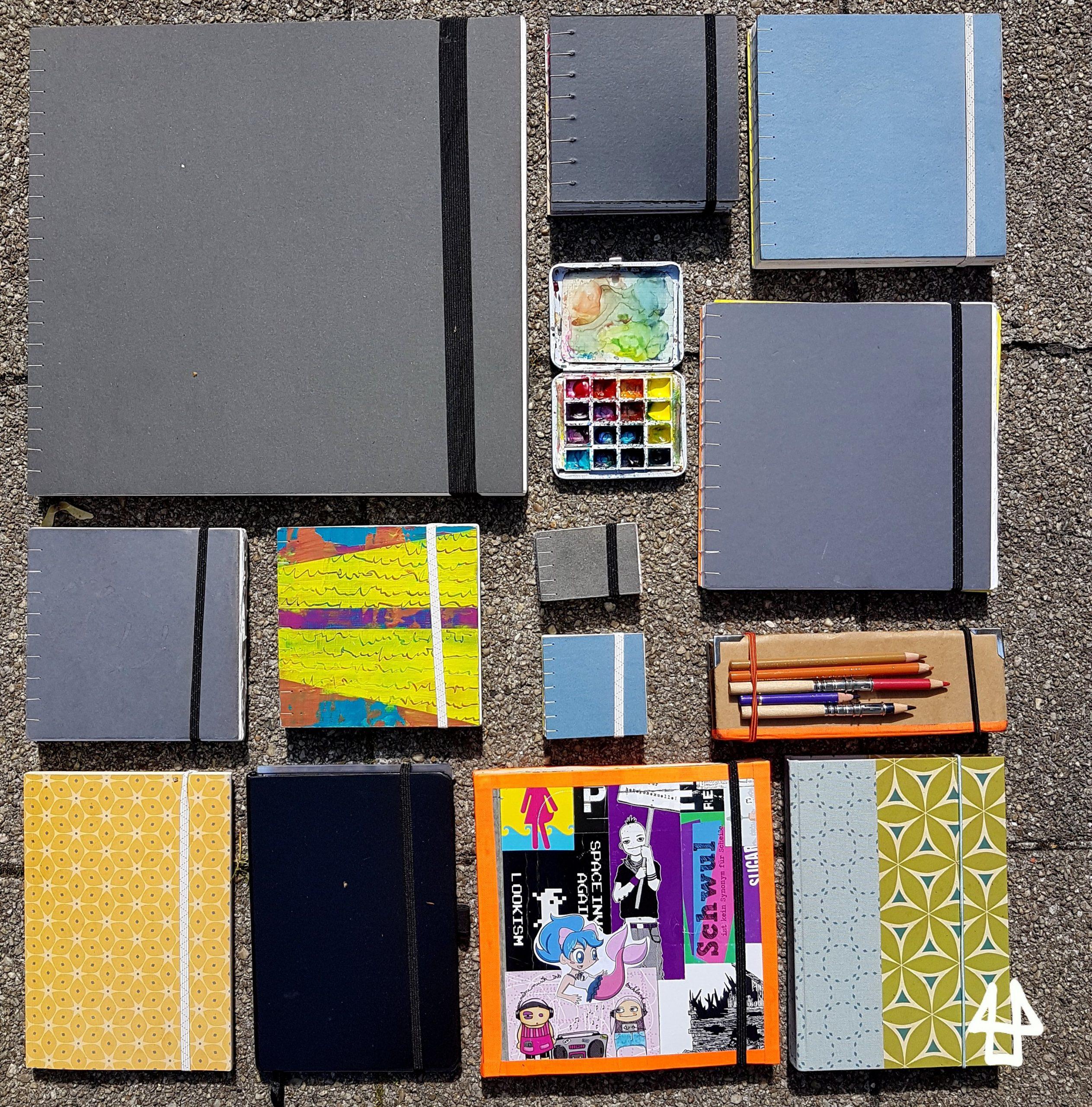 Auf Gehwegplatten liegen wie ein Puzzle angeordnet 12 hauptsächlich quadratische Skizzenbücher, dazwischen Maluntensilien