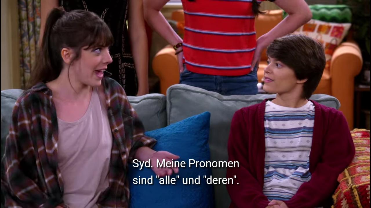 Syd mit Flannelhemd und braunem Pferdeschwanz stellt sich vor: Syd. Meine Pronomen sind alle und deren.