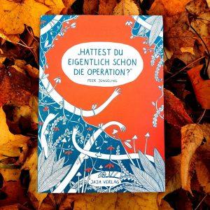 Das Buch, Hattest du eigentlich schon die Operation, mit türkisgrünem und leuchtorganenem Cover liegt auf orangegelbem Herbstlaub.