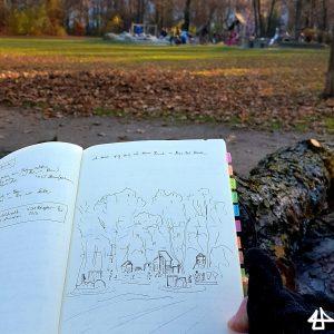 Foto: geöffnetes Skizzenbuch mit Füller-Zeichnung von Spielplatz unter großen Bäumen, im Hintergrund dieser Spielplatz.