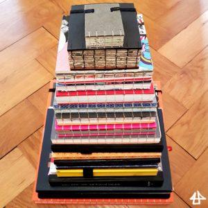 19 Bücher, handgebunden und industriell gefertigt, wie ein Turm übereinander, das größte zu unterst, das kleinste ganz oben.
