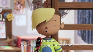 Ausschnitt des Zeichentrickfilms. Kinderzimmer mit hölzernem Stockbett und Pinnwand. Ein Kind mit Sidecut und blond gefärbter halblanger Haarmähne spricht in eine pinke Haarbürste. Die Untertitel im Bild lauten: Ich bin Thomas. Für mich benutzt man das Pronomen »xier«.