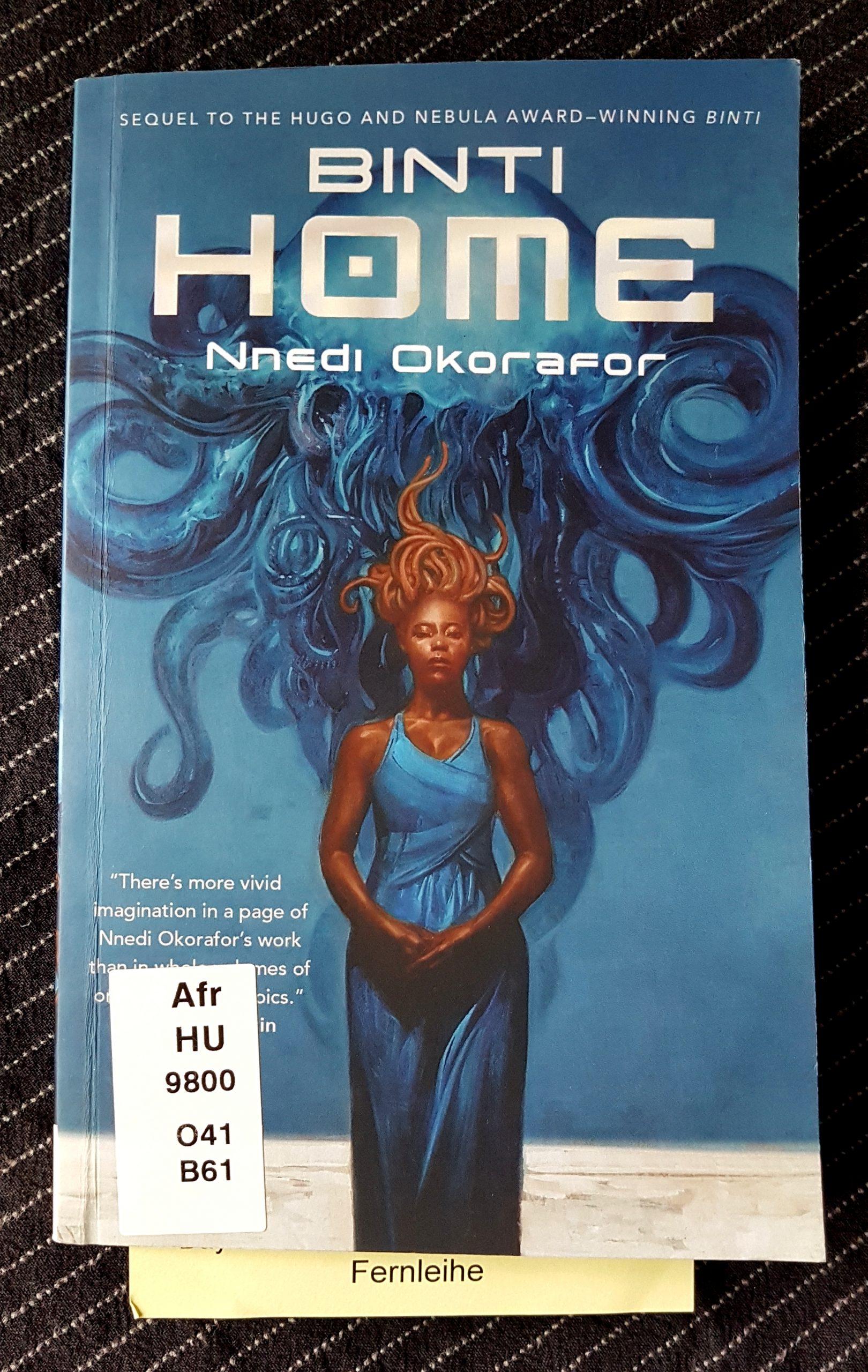 Buchdeckel von »Binti Home« von Nnedi Okorafor. Vor blauen Hintergrund eine schwarze Frau mit blauem Kleid und orange roten Tentakeln statt Haaren. Dahinter eine ebenso große blaue Qualle mit nach unten gehenden Tentakeln. Aus dem Buch guckt ein Zettel mit dem Wort Fernleihe.