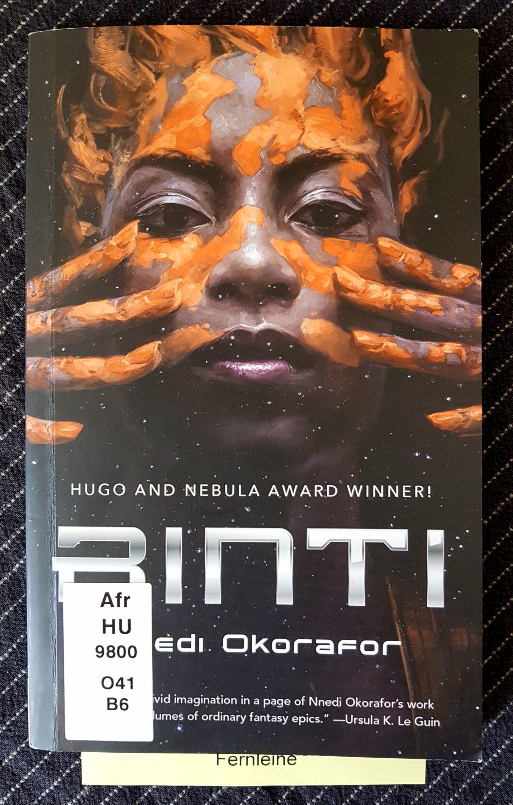 Buchdeckel von »Binti« von Nnedi Okorafor. Vor dunklem Hintergrund trägt ein junge schwarze Frau mit den Fingern ockerfarbenes Otjize in der Tradition der OvaHimba auf ihr Gesicht und die Haare auf. Sie schaut direkt in die Kamera. Aus dem Buch guckt ein Zettel mit dem Wort Fernleihe.