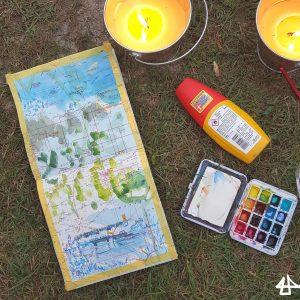 Foto von angefangener Zeichnung im Skizzenbuch. Daneben Mückenmittel, winziger Aquarellkasten und Zitronella-Kerzen.