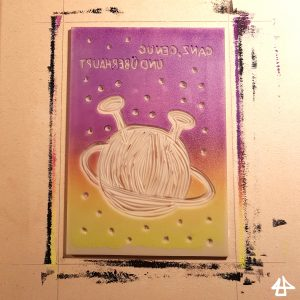 Linolplatte mit ausgeschnittenem Planeten mit Umlaufbahn und Antennen und spiegelverkehrtem Text ist mit einer dünnen Schicht Farbe im Farbverlauf von oben lila nach unten gelb eingefärbt.