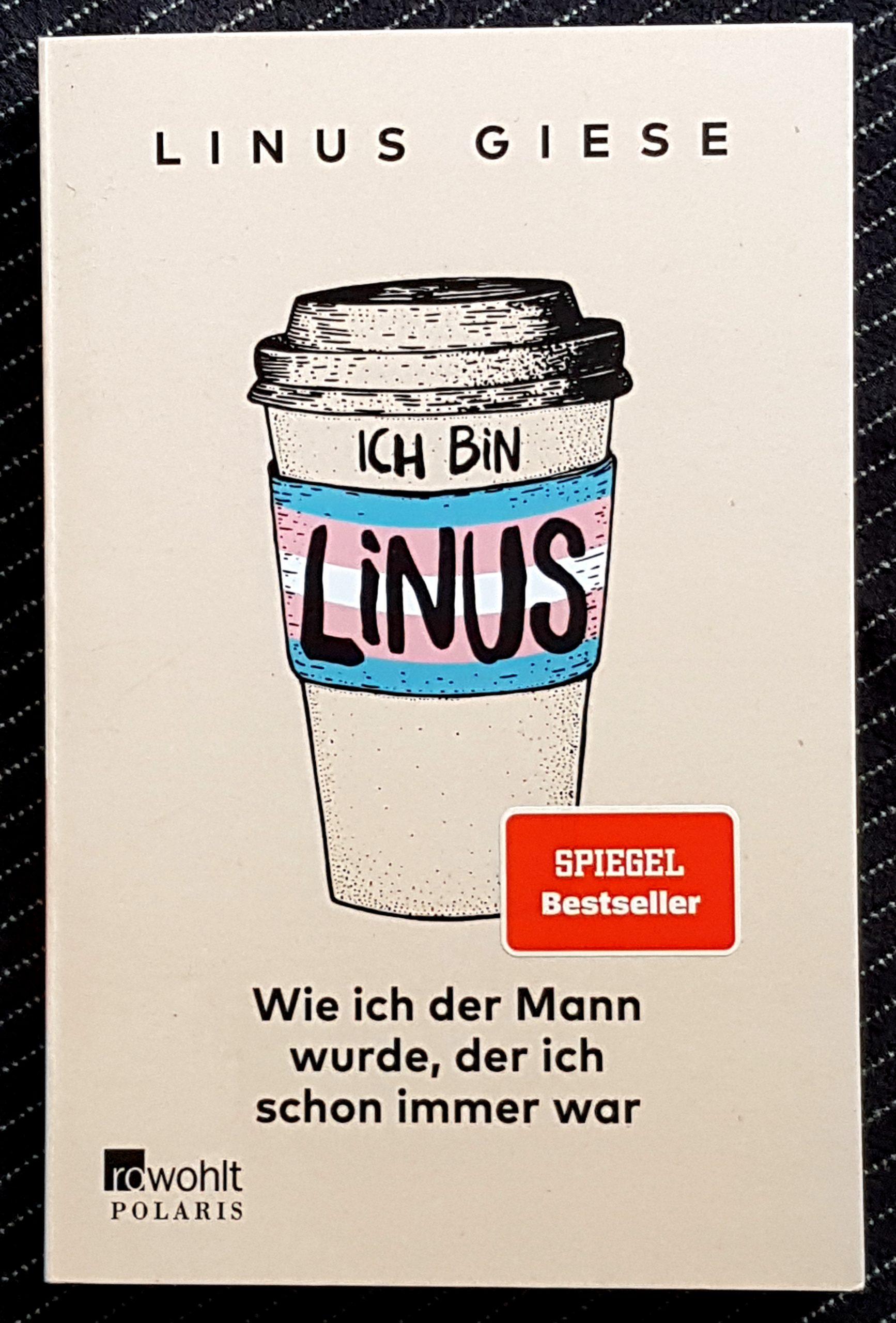 Buchdeckel von »Ich bin Linus - Wie ich der Mann wurde, der ich schon immer war« von Linus Giese. Der Autorenname auf beige-farbenen Grund, darunter ein gezeichneter To-Go-Becher beschriftet mit dem ersten Teil des Titels und der trans Flagge in hellblau-rosa-weiß, darunter der restliche Titel und der Verlag Rowohlt Polaris. Ein roter Aufkleber mit Spiegel Bestseller klebt auf dem Buch.
