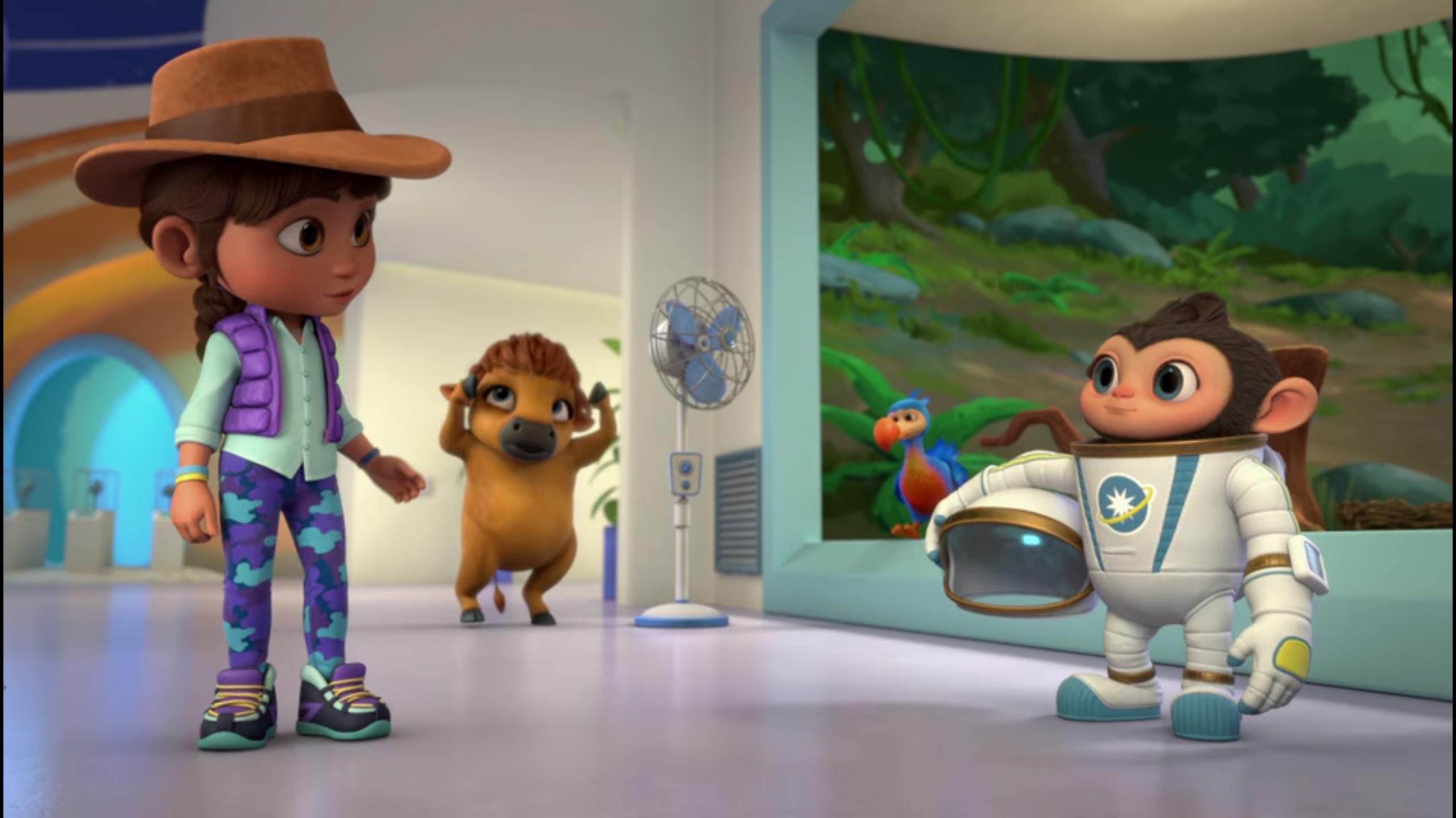 Standbild aus der Trickfilm-Serie: ein Kind mit Cowboy-Hut spricht in einem Museumsraum mit einem Äffchen in einem Weltraumanzug. Dahinter ein wenig entfernt ein Bison auf den Hinterhufen, dass sich mit beiden Händen über die eigenen Hörner streicht.