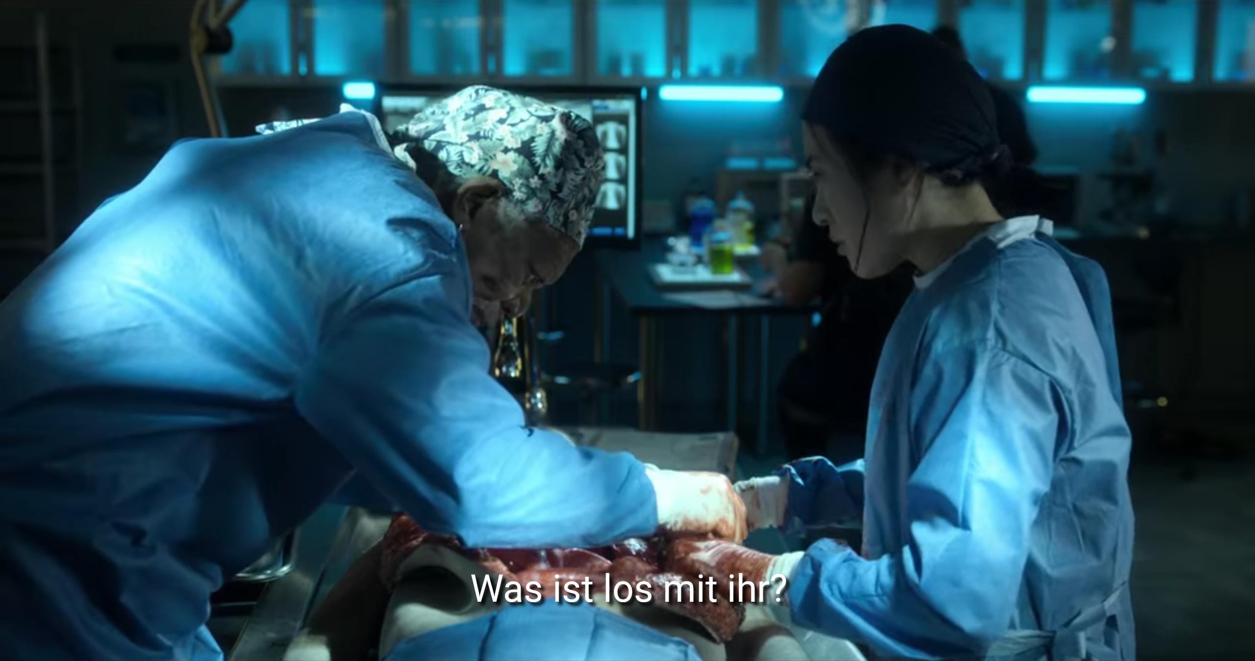 Filmstandbild mit Untertitel: >Was ist los mit ihr?<. Ein Operationssaal in bläulichem Licht, zwei Personen mit blauen Schutzkitteln operieren zusammen einen Dritten. Eine Person mit gemusterter Kopfdeckung, die andere mit schwarzen Haaren.