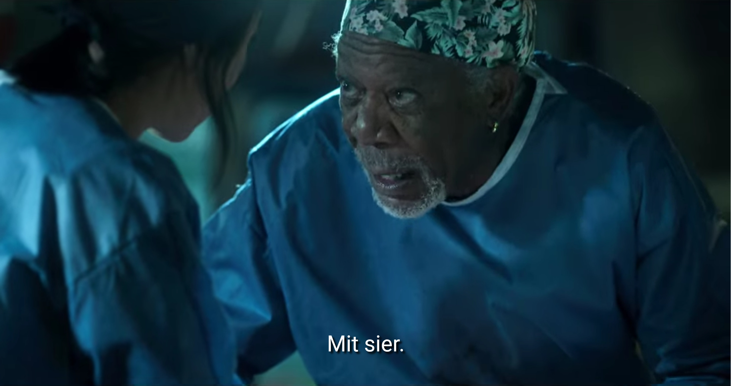 Filmstandbild mit Untertitel: >Mit sier!<. Die Person mit Kopfbedeckung hat einen weißen Henriquatre-Bart, einen Ohring und schaut hoch.