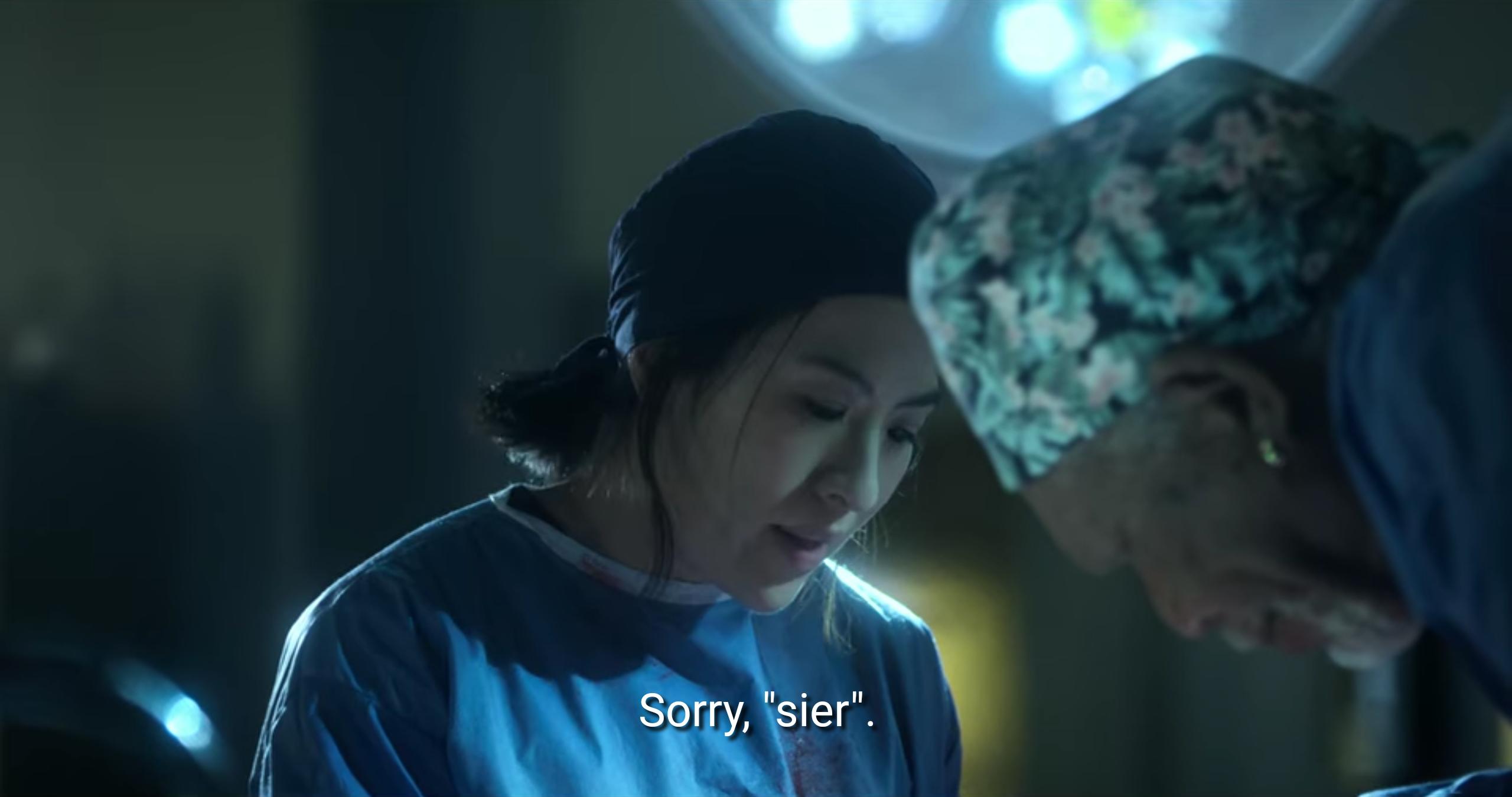 Filmstandbild mit Untertitel: >Sorry sier.< Die Person mit schwarzen Haaren hat einen kurzen Zopf im Nacken und spricht. Beide schauen nach unten
