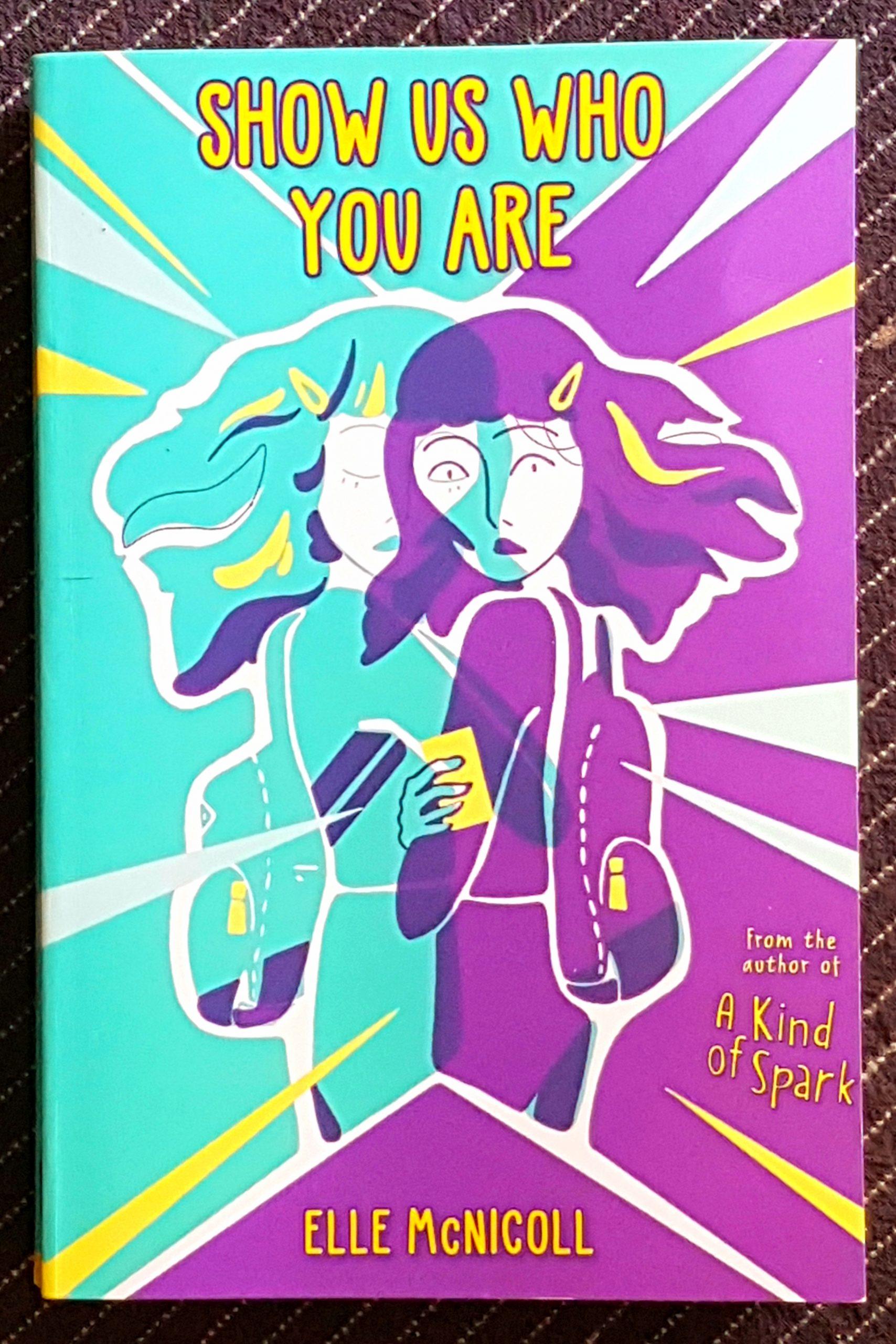 Buchdeckel von »Show us who you are« von Elle McNicoll. Der Titel ganz oben in gelb und der Name ganz unten in gelb. Die Illustration im drei-Farbendruck in gelb, türkis und lila. Die Silhouetten von zwei Personen überlagert sich, es scheint die gleiche Person mit langen Haare, gelber Spange und Rucksack zu sein. Die türkis farbene Person schaut mit verschränkten Armen konzentriert nach unten. Die Person in lila ist so überlagert, dass ein Auge an gleicher Position ist, die Augen sind weit aufgerissen und schauen direkt nach vorn, in der Hand ein gelbes Handy. Von ihnen beiden weg gehen weiße und gelbe Dreiecke wie Blitze nach außen.
