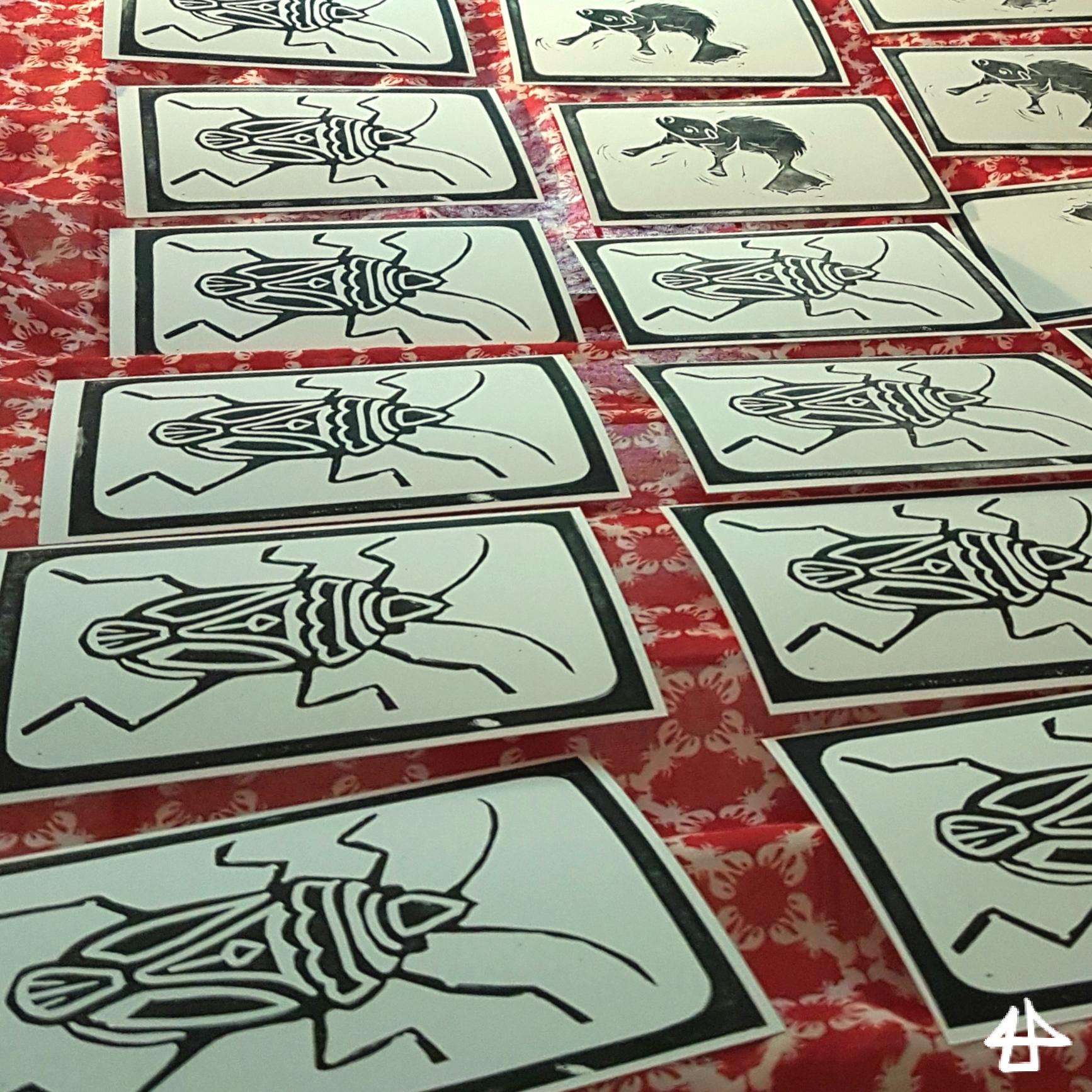 Foto von vielen bedruckten Postkarten, schwarz auf weiß, die auf einen rot-weiss gemusterten Tuch liegen. Im Vordergrund ist das Motiv des Linoldruckes eine Wanze und im Hintergrund sind auch vereinzelte Ottermotive.