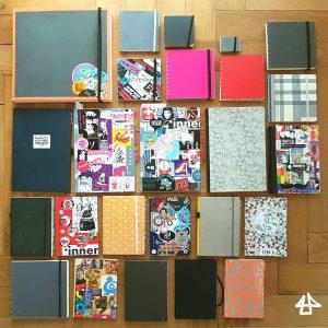 Foto von 25 Büchern, quadratisch und DIN Format die nach Größe geordnet auf einem Packetfussboden liegen. 10 sind in verschiedene Grautönen, ein pinkes, eine rotes, 5 bunt bedruckte und 8 mit zahlreichen Aufklebern beklebt.