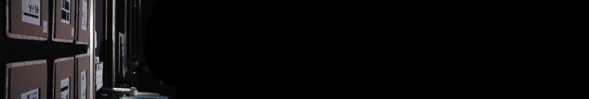 Foto gehängter Minicomics in einem schwarzen Saal.